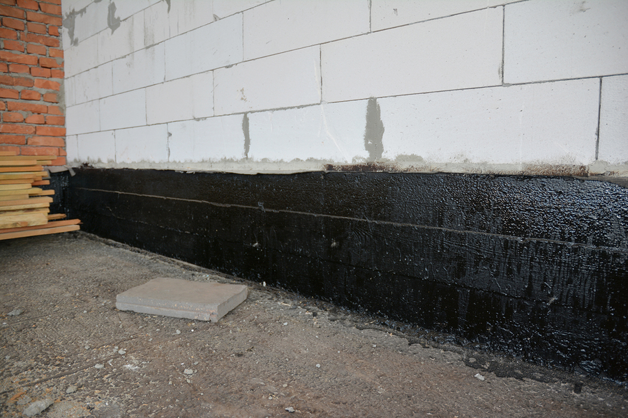 foundation bitumen waterproofing. building house construction with waterproofing spray-on tar. construction techniques for spraying waterproofing basements and foundations.
